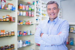 Portrait of a smiling pharmacist standing with arms crossed in the pharmacy